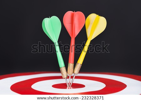 Closeup of darts on target isolated over black background - stock photo