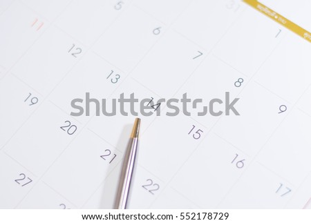 Closeup of dates on calendar page with pen