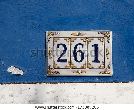 closeup of decorated ceramics house number digits sign on the wall - stock photo
