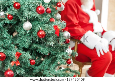 Closeup of decorated Christmas tree with Santa Claus sitting in background outdoors - stock photo