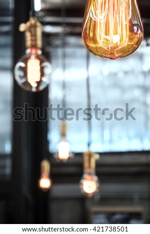Closeup of decorative antique edison style light bulbs with factory materials background. Copyspace. Bottom view. - stock photo