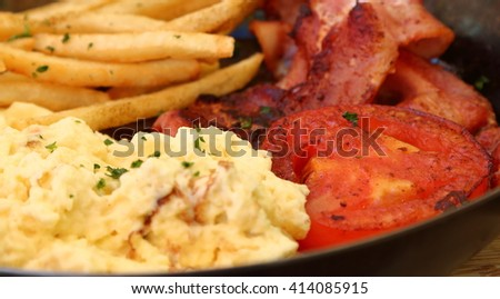 Closeup of delicious breakfast - bacon,scrambled eggs, grilled tomato and fries in a pan - stock photo