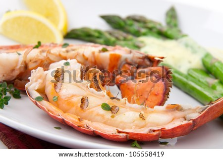 Closeup of delicious grilled lobster tails served with asparagus and bearnaise sauce - stock photo