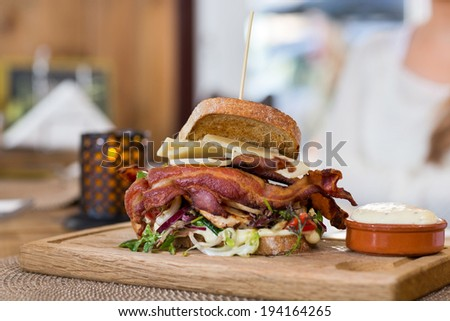 Closeup of delicious sandwich on wooden plate in restaurant - stock photo