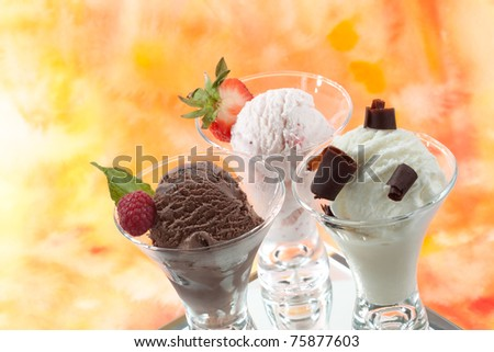 Closeup of delicious vanilla, strawberry, and chocolate ice cream with fresh berries, mint, and chocolate swirls. - stock photo