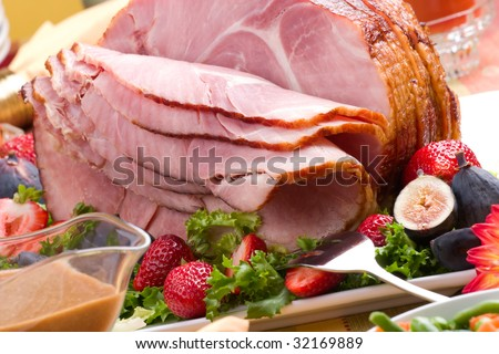 Closeup of delicious whole baked sliced ham with fresh strawberries and figs on holiday table.