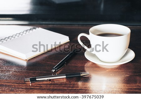 Closeup of desktop with coffee cup, two pens and notepad - stock photo