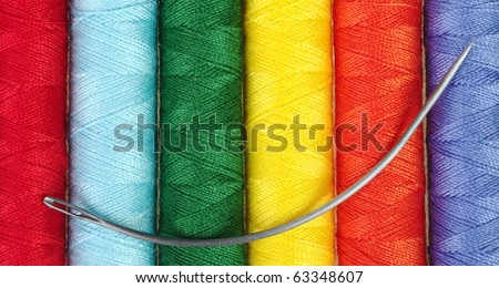 closeup of different colored sewing thread with circular mattress thread on top