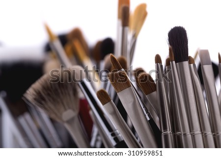 Closeup of different professional natural soft make-up brushes for eyeshadow powder and facial foundation for visagistes black and brown colors on white background, horizontal picture - stock photo