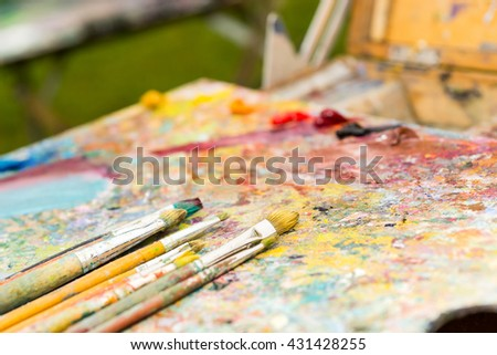 Closeup of different time-worn paintbrushes on an old colorful palette - stock photo