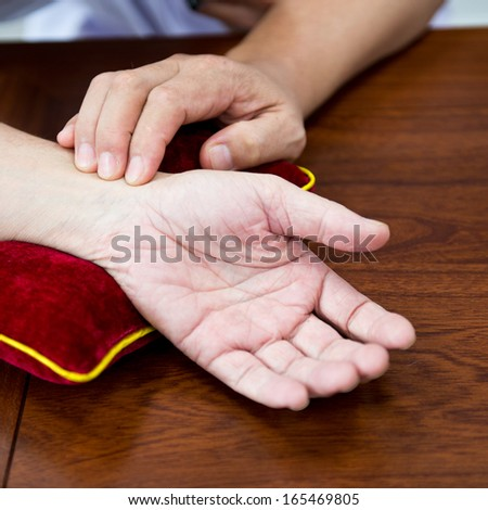 Closeup of doctor checking heartbeat and pulse on patient's wrist. - stock photo