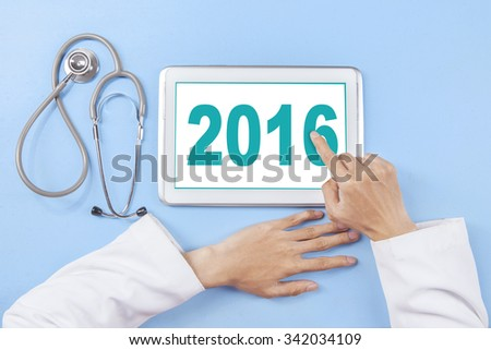 Closeup of doctor hand using a tablet screen to write number 2016 near the stethoscope - stock photo