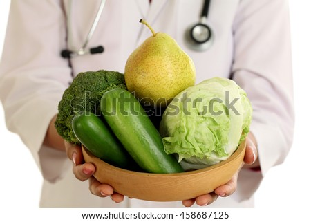 Closeup of doctor holding a bowl of vegetables against white background - stock photo