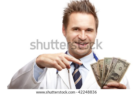 Closeup of doctor holding a  bundle of us dollar bills in his hand and points with other hand on it. Isolated on white. - stock photo