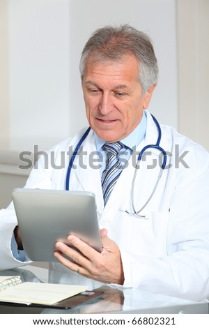 Closeup of doctor in the office with electronic pad - stock photo