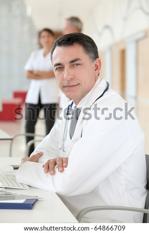 Closeup of doctor sitting in his office - stock photo