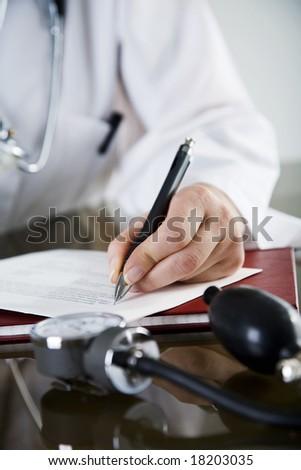 closeup  of doctor writing a prescription - stock photo