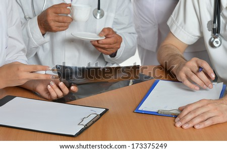 Closeup of doctors hands having a discussion at table - stock photo