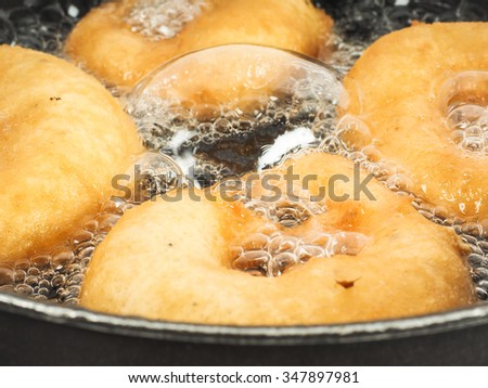 Closeup of donuts cooking in boiling oil in kettle - stock photo