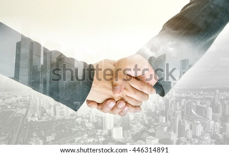 Closeup of double exposure handshake of business peoples on the city background. - stock photo