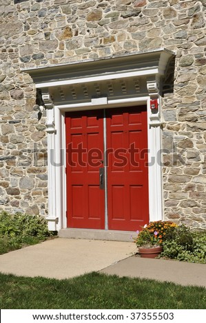 closeup of double red doors for an old stone church