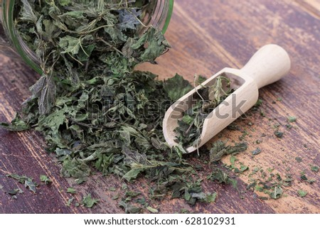 Closeup of dried nettle leaves in glass with wooden spoon on scratched, dark wood