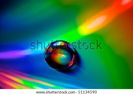 Closeup of drops of water (with beautiful reflections) on a multicolored surface - stock photo