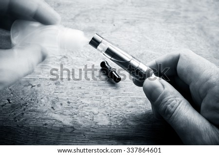 closeup of e-cigarette  filling on wooden background  - stock photo