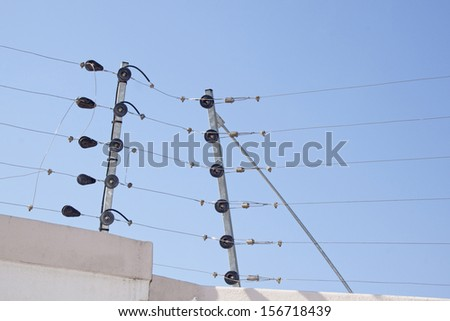 Closeup of electric fence instalation on boundary wall against blue sky - stock photo