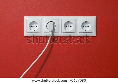 Closeup of electrical outlets, cable and electric plug on red textured wall - stock photo