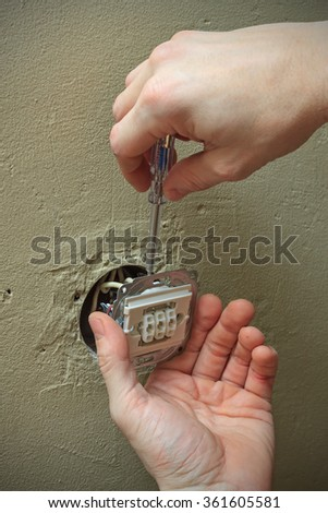 Closeup of electrician hands with screwdriver installing light switch in wall - stock photo