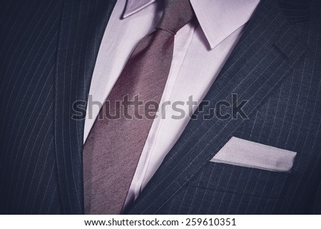 Closeup of elegant formal business suit with dark grey jacket with handkerchief in the pocket, shirt and necktie. - stock photo