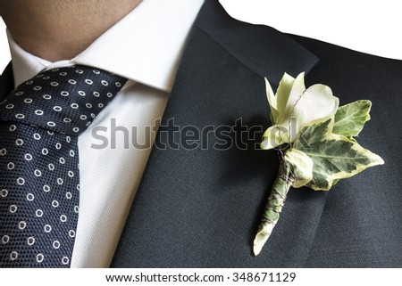 Closeup of elegant man in blue suit with flagship and polka dot tie isolated
