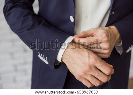 Closeup of elegant young fashion man dressing up for wedding celebration. Color close up image of male hands. Handsome groom dressed in modern blue formal suit, white shirt getting ready for event.