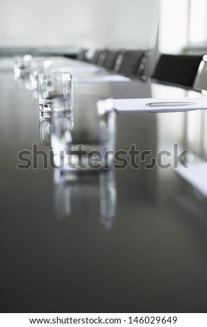 Closeup of empty glasses on conference table in office - stock photo