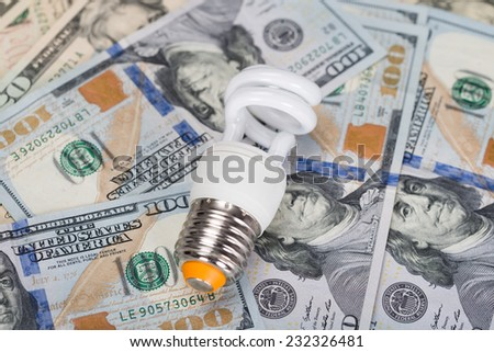 Closeup of energy saving bulb on dollar bills - stock photo