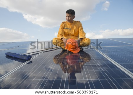 Closeup of engineers  or worker hold in hand orange helmet wearing orange bear coat. Sitting on a solar cell.