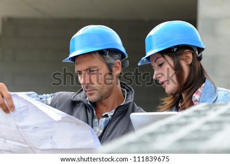 Closeup of engineers reading plan on building site - stock photo