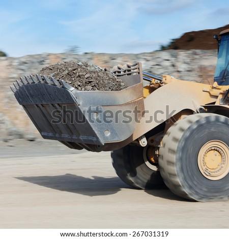 Closeup of excavator carrying stones on road - stock photo