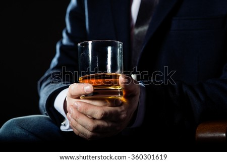 Closeup of executive holding  whiskey to illustrate executive privilege concept - stock photo