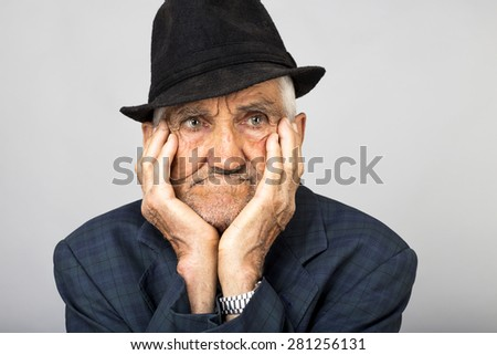 Closeup of expressive old man holding face in his hands over gray background - stock photo