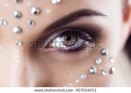 Closeup of eye luxury party make-up. Beauty woman makeup with crystals on face - stock photo