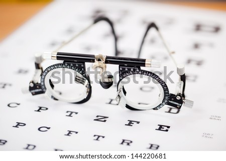 Closeup of eye test glasses on Snellen chart - stock photo