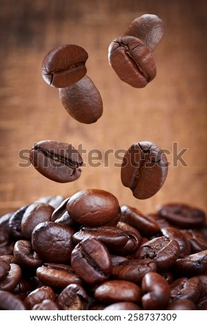 Closeup of falling coffee beans on dark background