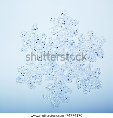 Closeup of falling snowflake on clear blue background - stock photo