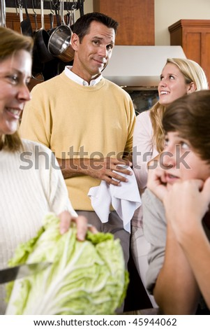 Closeup of family with two teenage children in kitchen - stock photo