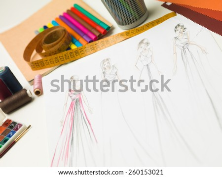 closeup of fashion designer workspace with sketches of evening gowns and designing equipment - stock photo