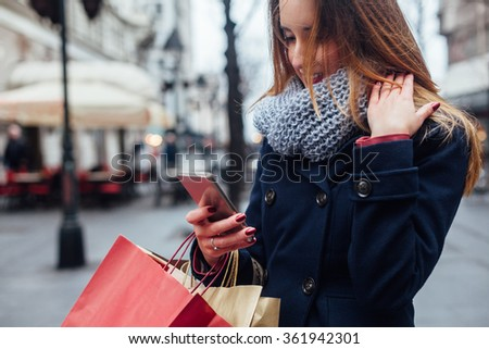 Closeup of fashionable woman texting on her mobile phone on the street - stock photo