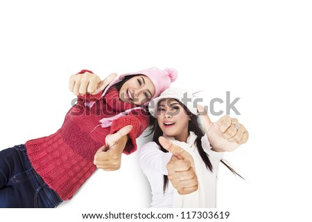 Closeup of fashionable women wearing winter clothes showing thumbs-up - stock photo