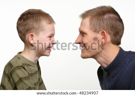 closeup of father and child with smiling excited faces looking at each other - stock photo